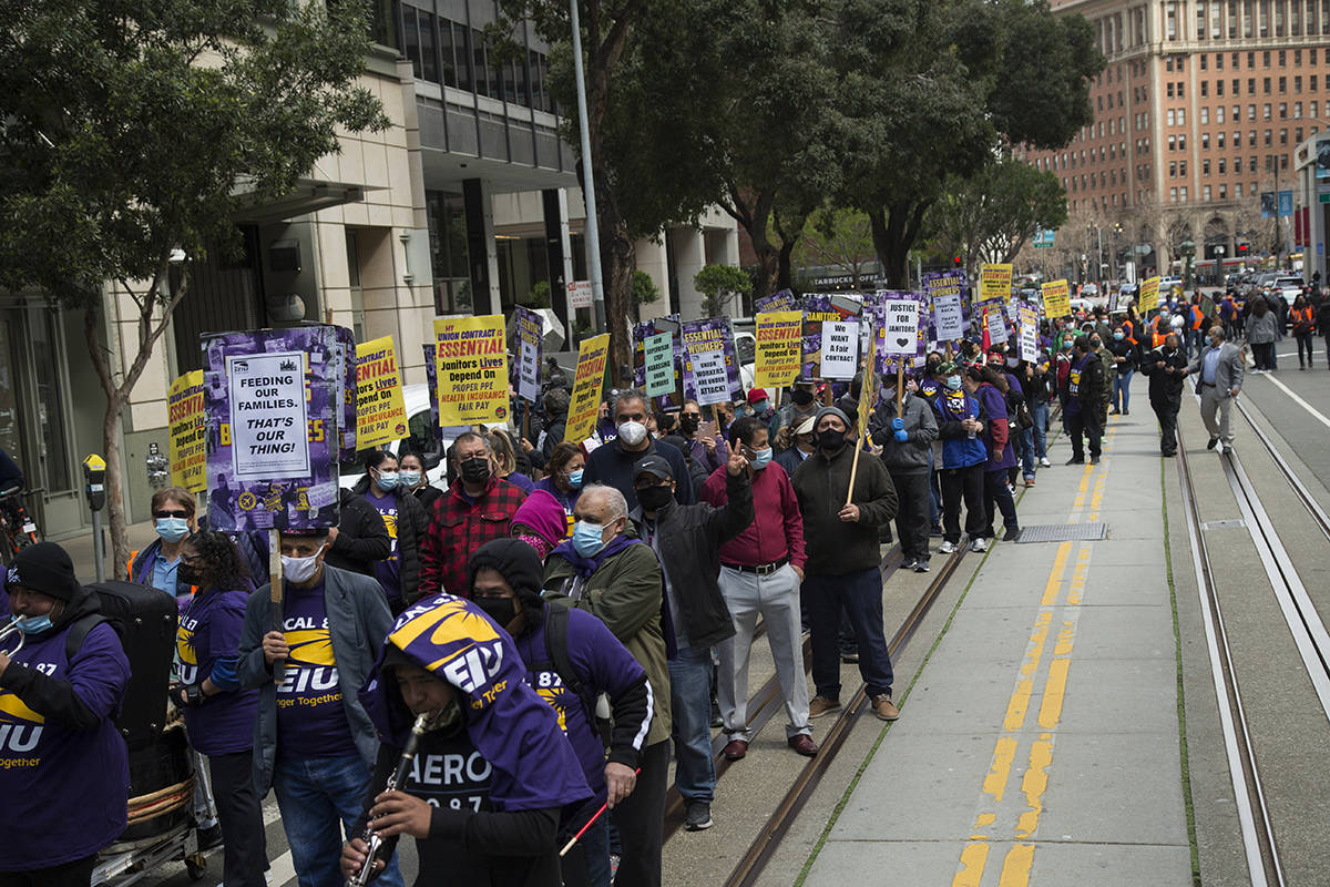 Hundreds of janitors with SEIU Local 87 march up California Street in downtown San Francisco on Monday, March 8, 2021. (Kevin N. Hume/S.F. Examiner)