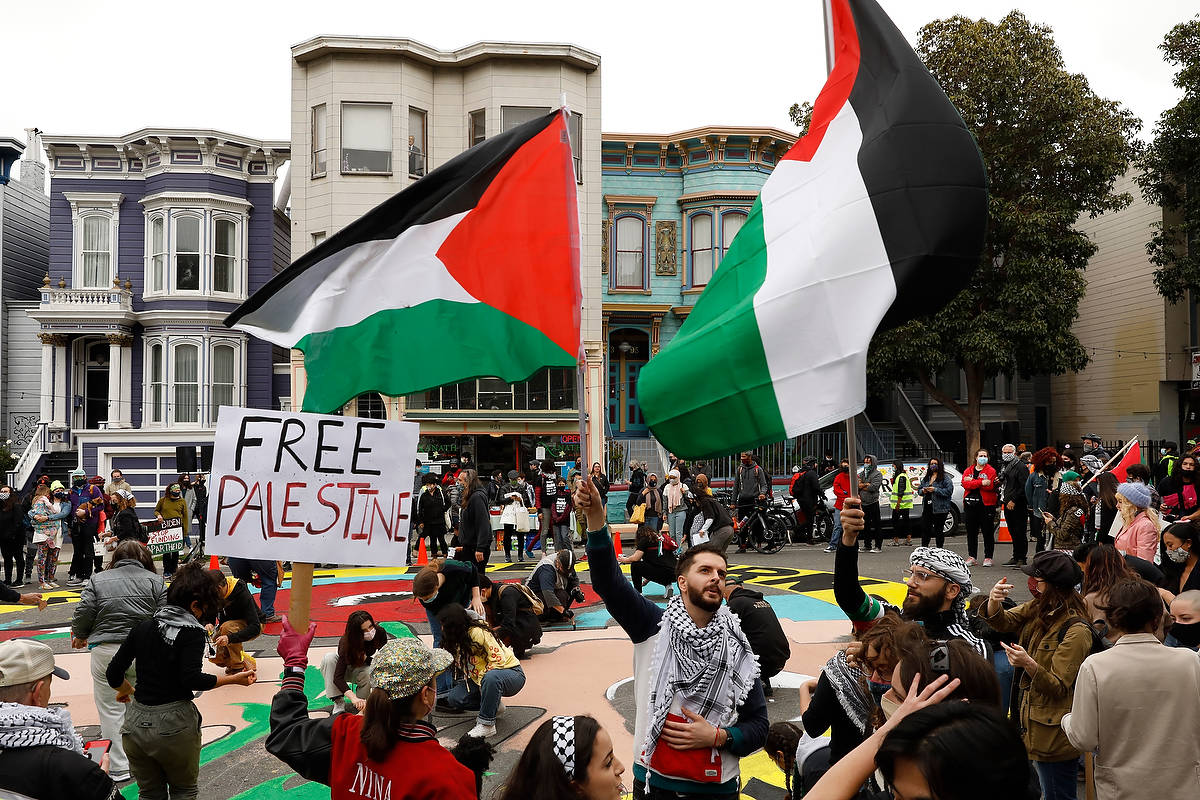 Feras Dalia (right) and Mohamed Rasheed (left) wave Palestinian flags at the Protest for Palestine on Saturday, May 15, 2021.. (CraigLee/Special to the S.F. Examiner)