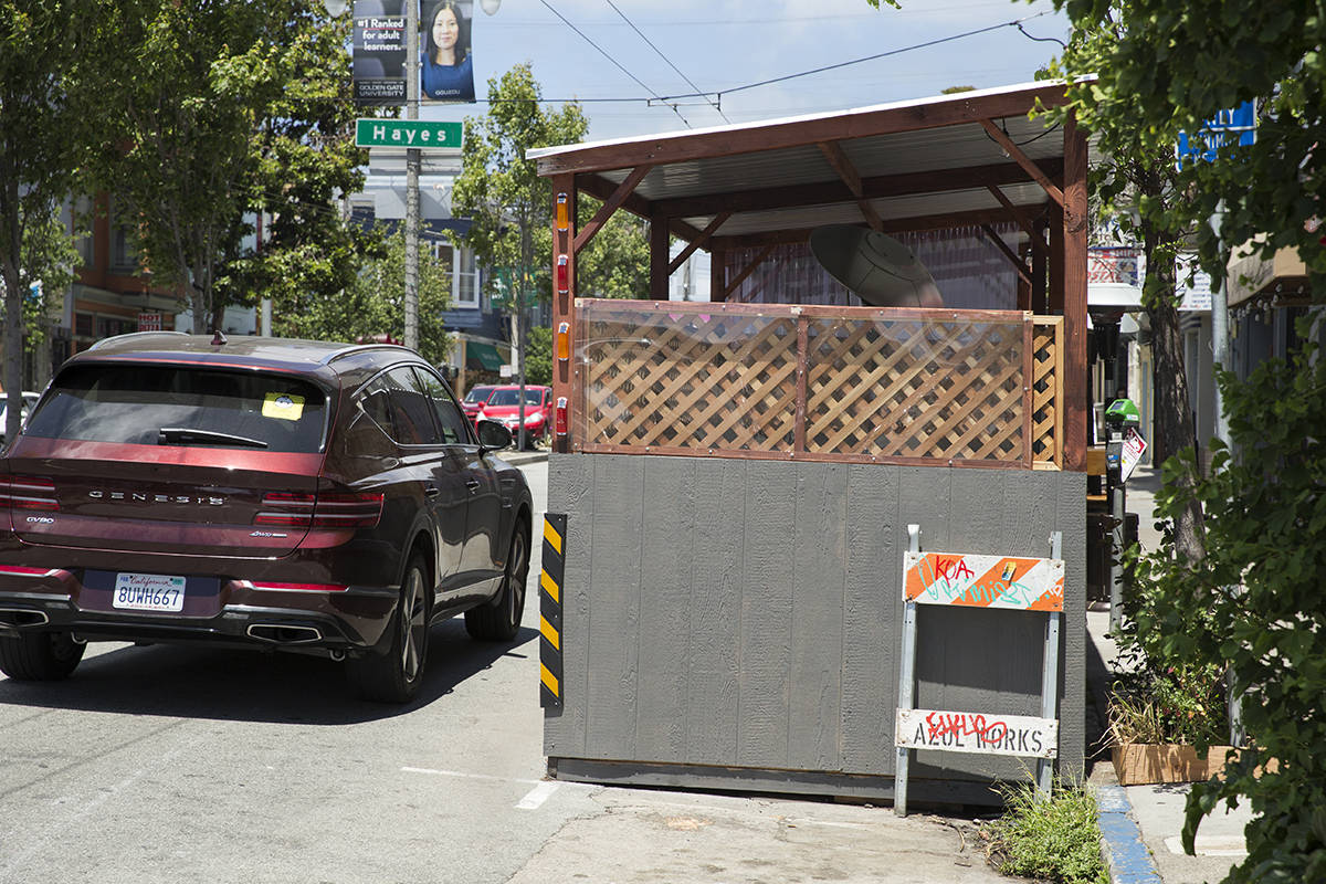 A car passes by a Shared Spaces parklet outside Horsefeather on Divisadero Street on Wednesday, June 23, 2021. The front section was recently repaired after a driver crashed into it in May. (Kevin N. Hume/The Examiner)