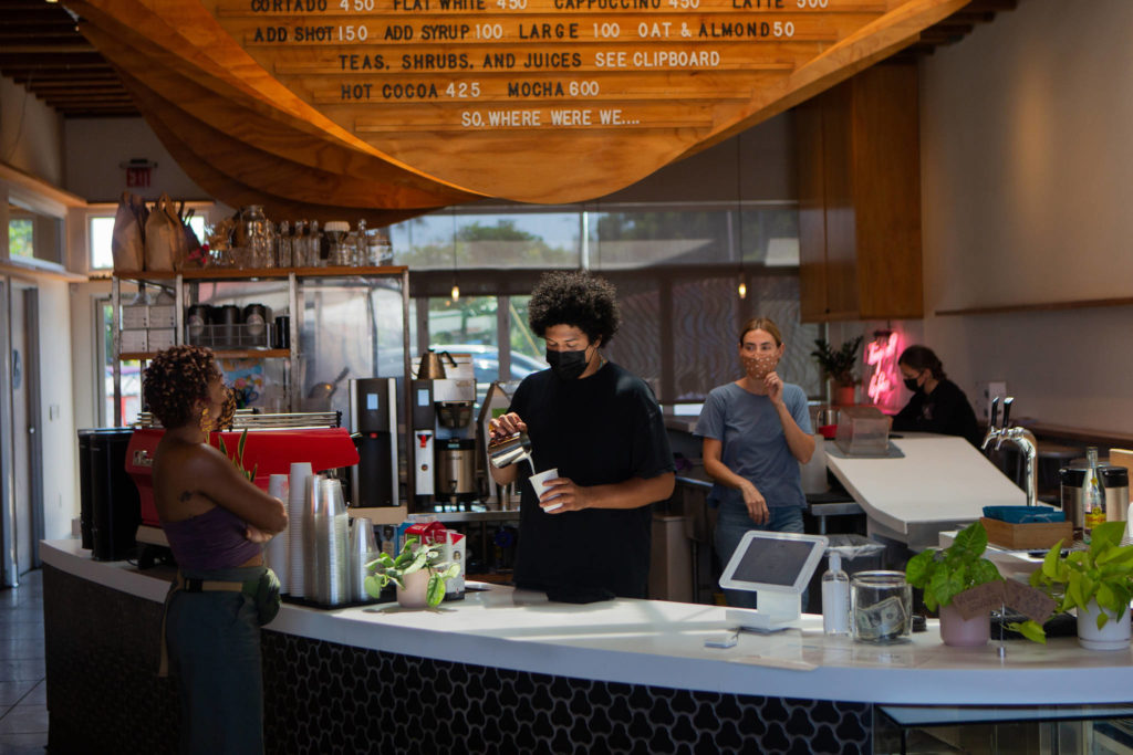 Employees wearing masks as they serve customers at Dinosaur Coffee on Sunset Boulevard in Los Angeles on July 27, 2021, where masks are required again indoors. (Alex Welsh/The New York Times)