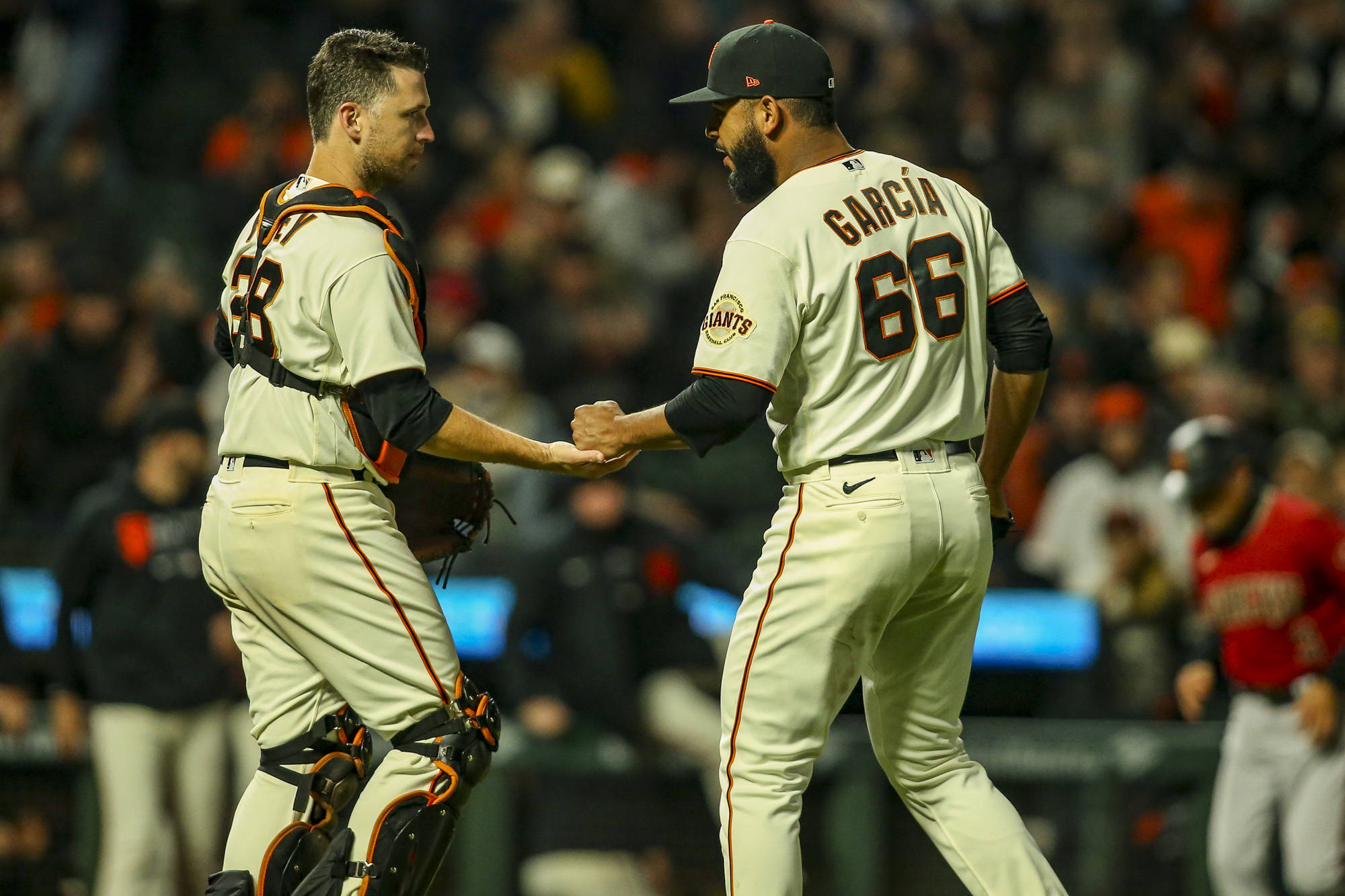Giants catcher Buster Posey, left, congratulated pitcher Jarlin Garcia after closing out the game with a save and the win over the Diamondbacks at Oracle Park on Aug. 11. (Chris Victorio/Special to The Examiner)