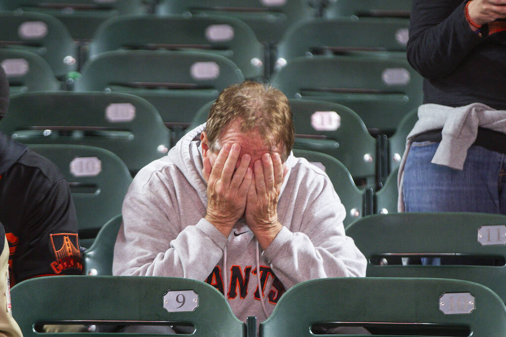 A Giants fans hangs his head in disbelief after the Dodgers won the NLDS in a controversial finish to a tight Game 5. (Chris Victorio/Special to The Examiner)