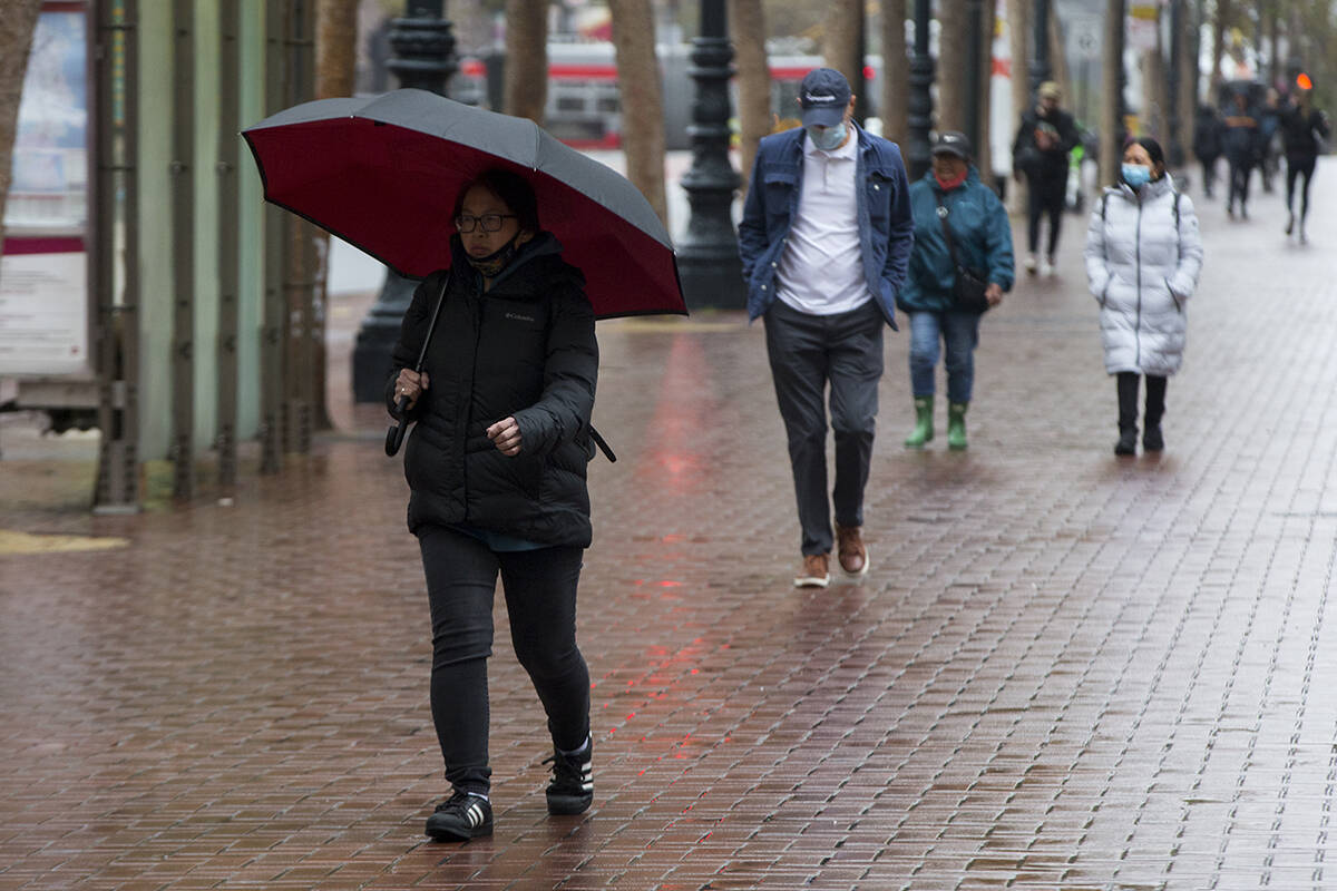 Badly needed rain cooled off pedestrians on Market Street in The City on Wednesday. (Kevin N. Hume/The Examiner)