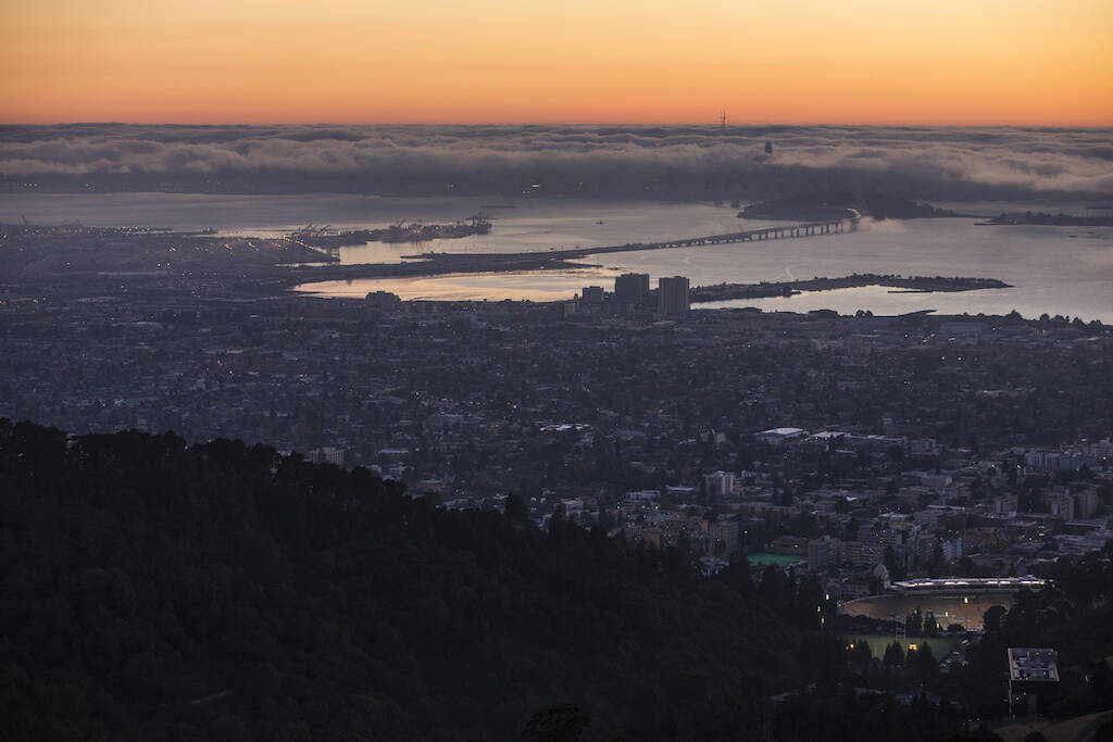 """The sun sets over the Bay Area, as seen from the Berkeley Hills, Oct. 18, 2017. """"The gauzy fantasy that we are so much better here in the Bay Area because of our diversity, because we are too focused on the future to get hung up on this region's ugly past, because we're so much cooler than everywhere else — lets white liberals pretend that the taint of racism can't reach them here in this shining city on a bunch of hills.""""(Andrew Burton/The New York Times)"""